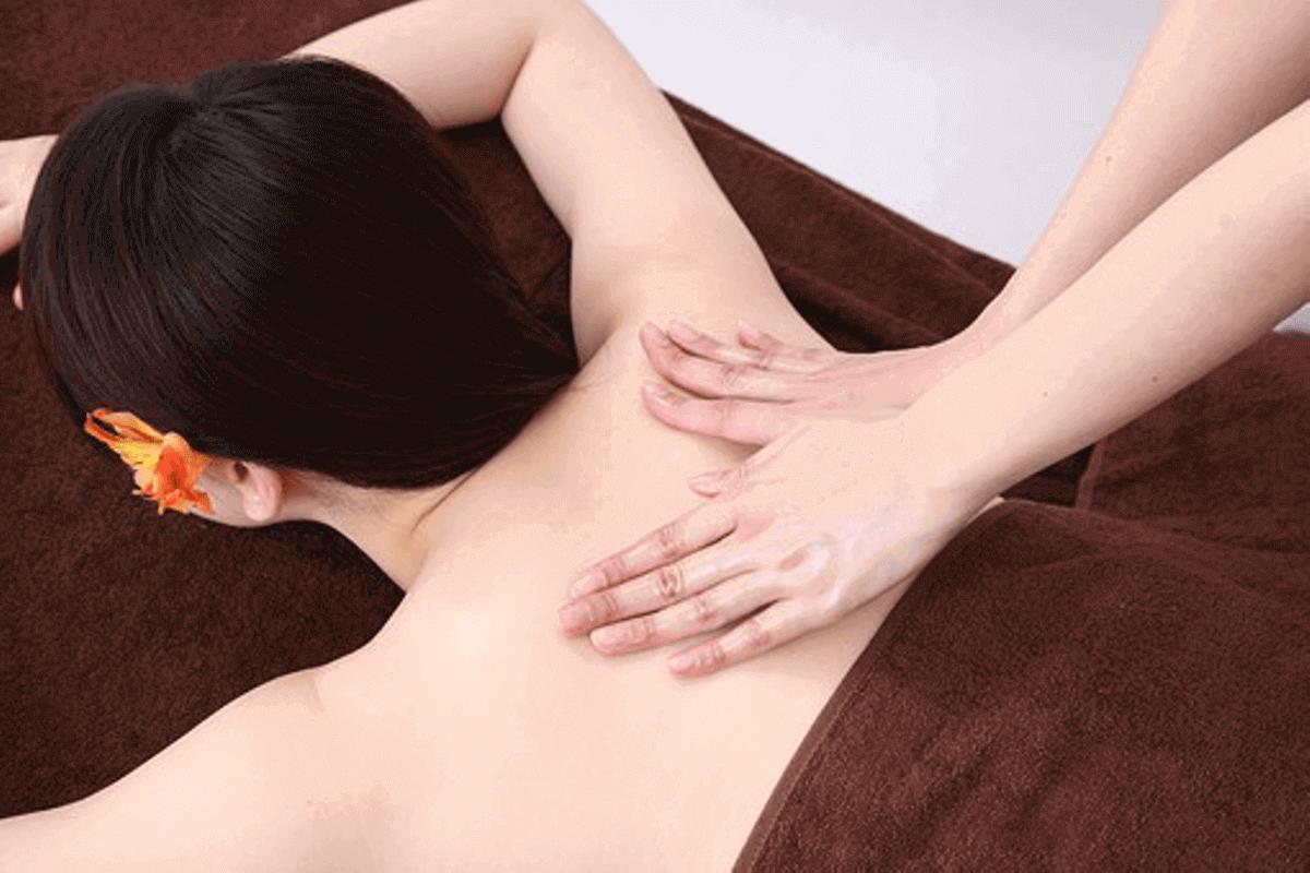 女性の背中をオイルマッサージ